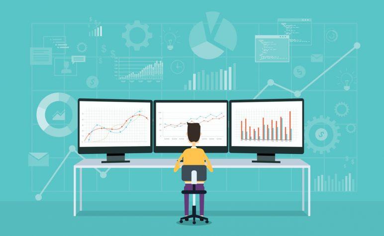 Человек сидит за компьютерами, на которых изображены графики